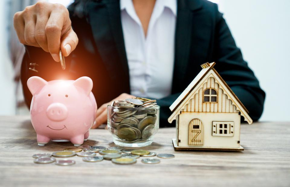Piggy bank and stacking gold coins with increase and There is light at the coin. Saving money for buy a new house and Investor  , Saving money for buy a new house and loan for plan business investment for real estate in the future concept.