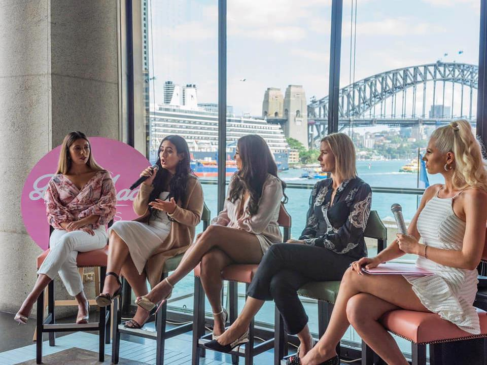 Hili speaks on a panel with 4 other women, backdrop is a river with a cruise ship