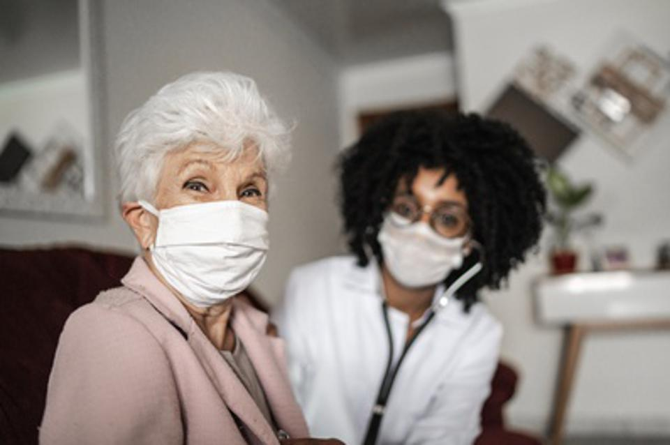 Portrait of health visitor and a senior woman during home visit