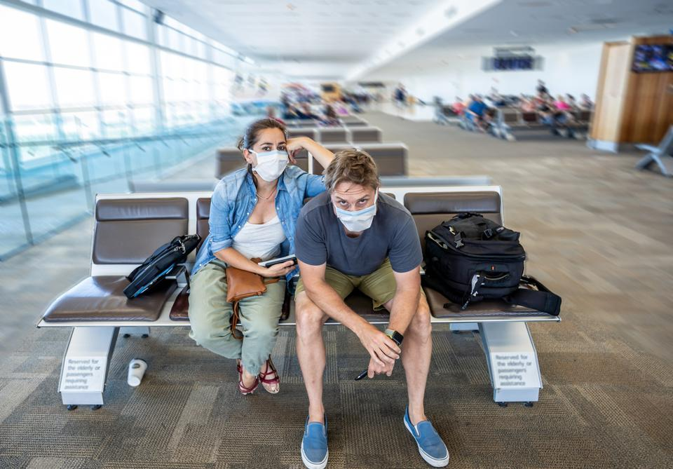 Coronavirus outbreak travel restrictions. Travelers with face mask at international airport affected by flight cancellation and travel ban. COVID-19 pandemic and countries shutdowns.