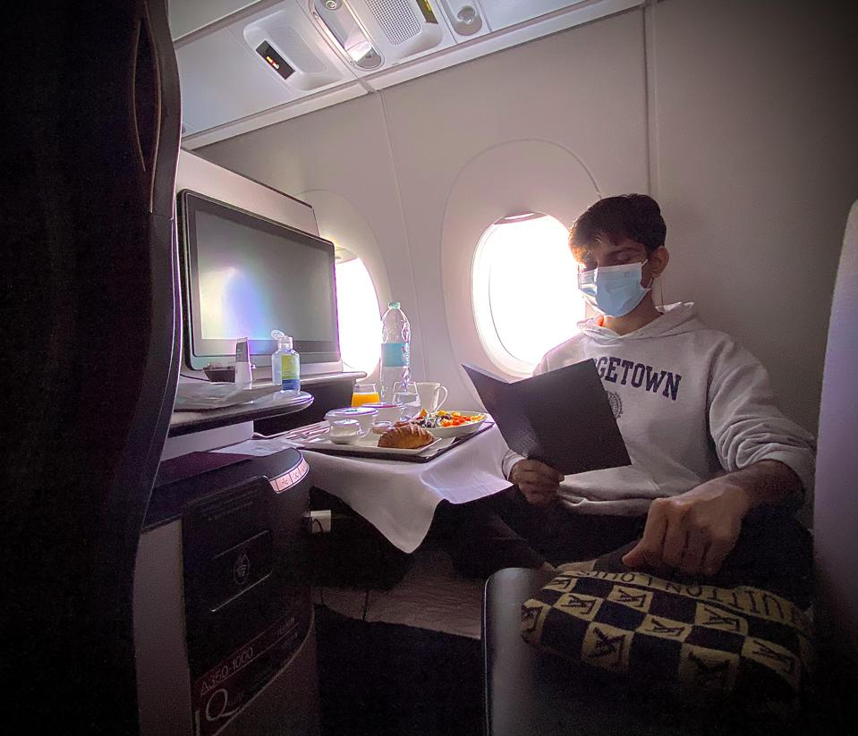 young man traveling first class flight during the coronavirus pandemic and eating food