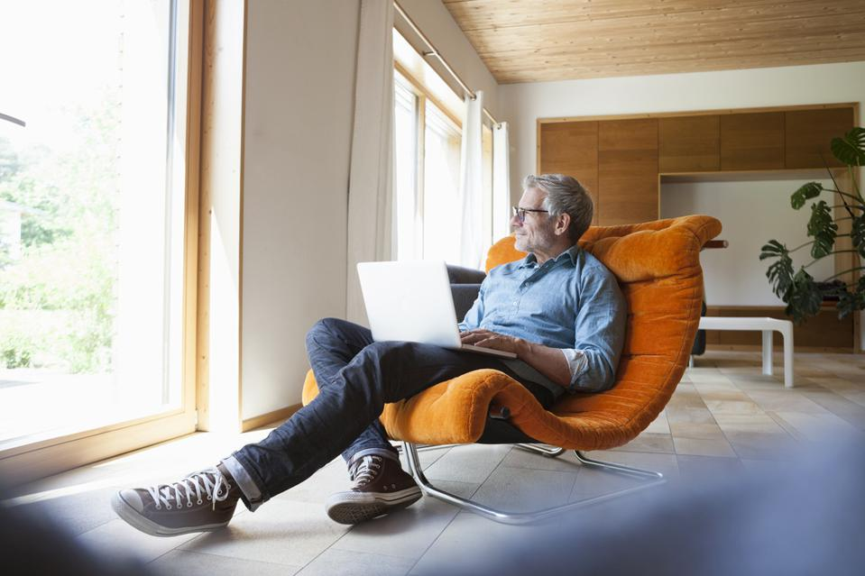 Mature man using laptop in armchair