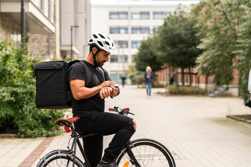 A delivery man is using a bike to transport food in the city