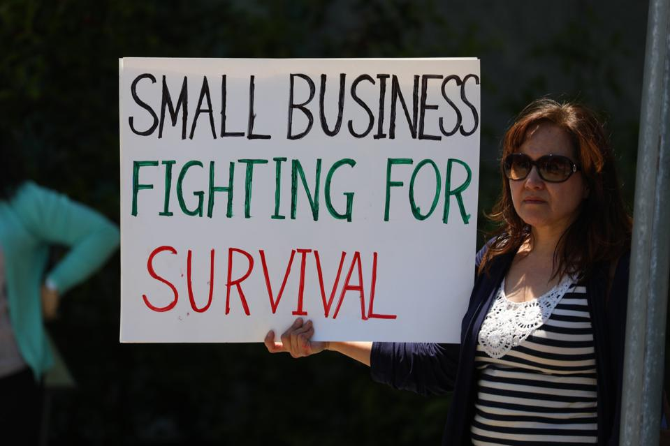 Small business owner holding up sign to survive this economy