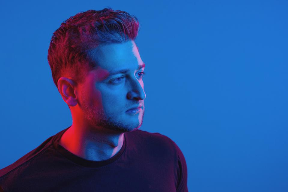 Dominik Zane is a startup founder. Thi is his portrait against a blue backdrop.