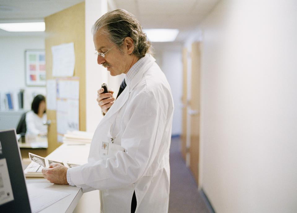 Doctor Dictating Notes into Voice Recorder