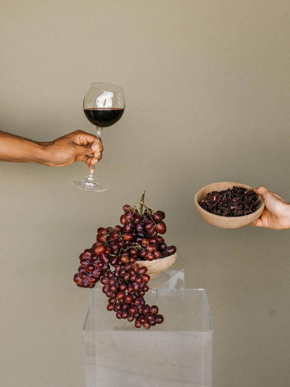 A wine glass, red grapes, and herbs.
