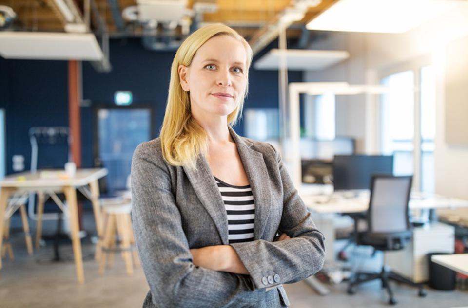 Confident mid adult businesswoman standing in office