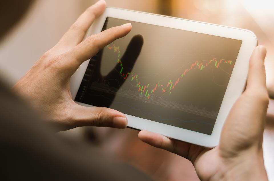 Man checking stock market chart on tablet