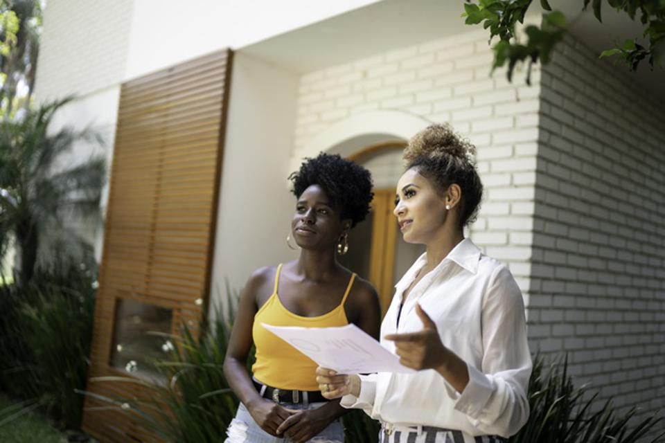 Real estate agent/financial advisor talking to a client in front of a house