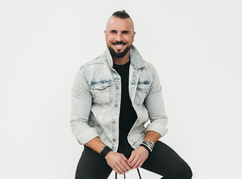 A fit man sits in a denim jacket, smiling.