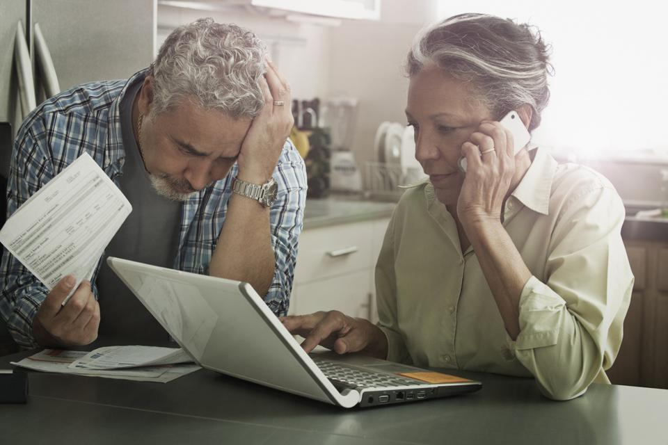 Stressed couple paying bills on laptop