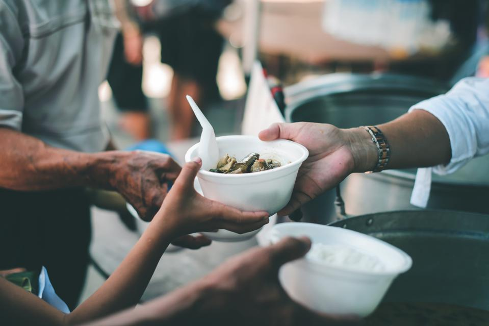 Hands serving food, other hands reach to accept