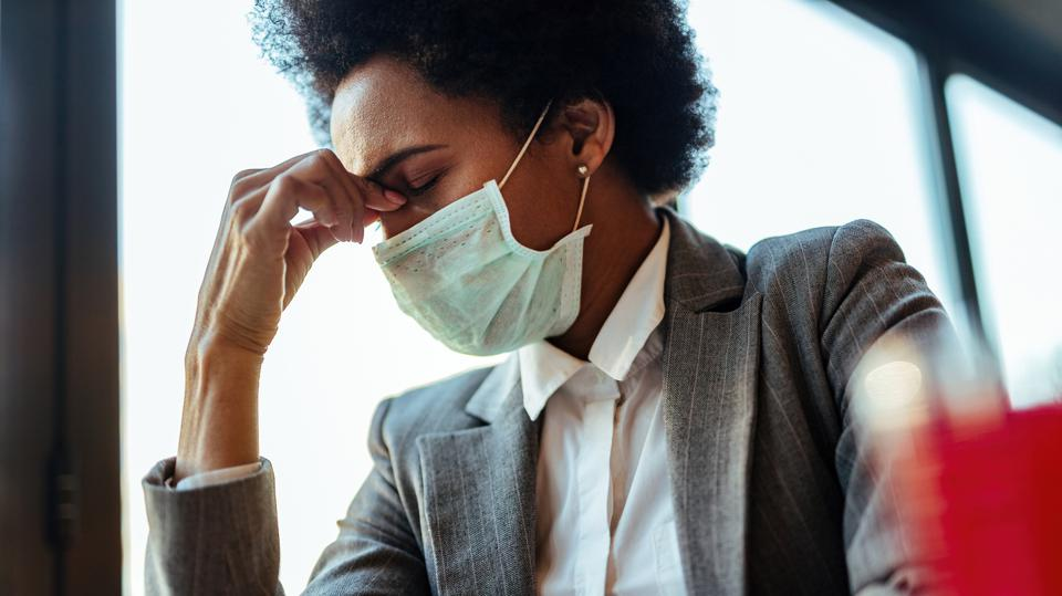 Black businesswoman with protective face mask holding her head in pain.