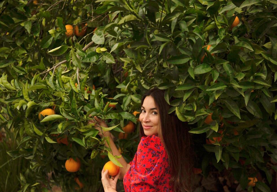 VERTLY founder Claudia Mata-Gladish in front of an orange tree