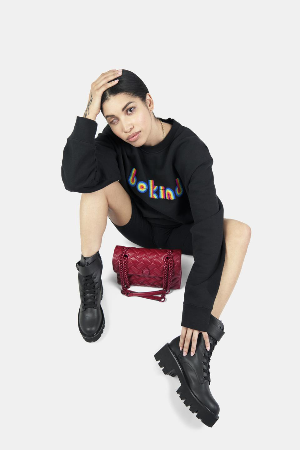 Model wearing Kurt Geiger be kind sweatshirt and recycled leather boots