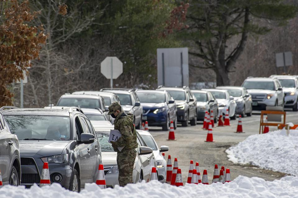 Cars wait in a long line as residents of Londonderry, New Hampshire, seek vaccinations.