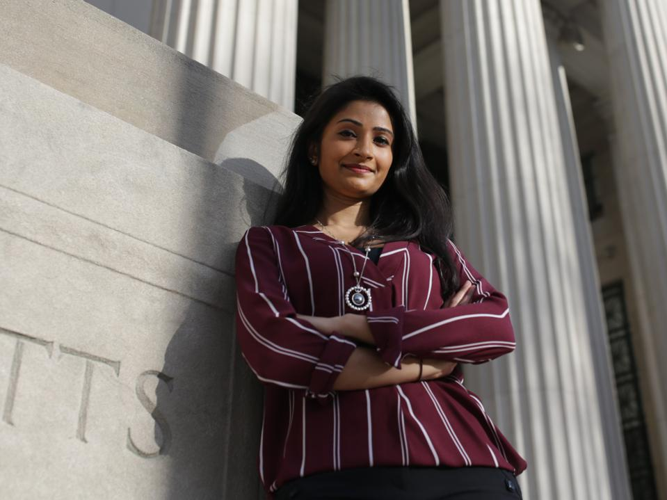 Shriya Srinivasan shown standing smiling leaning against an MIT building with columns.