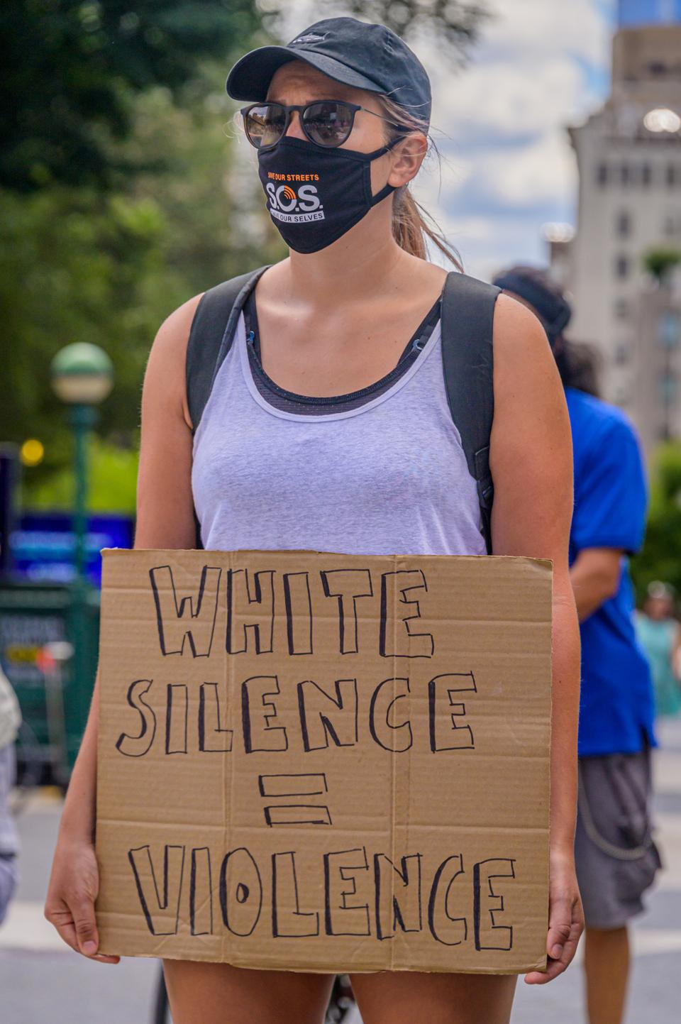 A participant holding a White Silence = Violence sign at the...