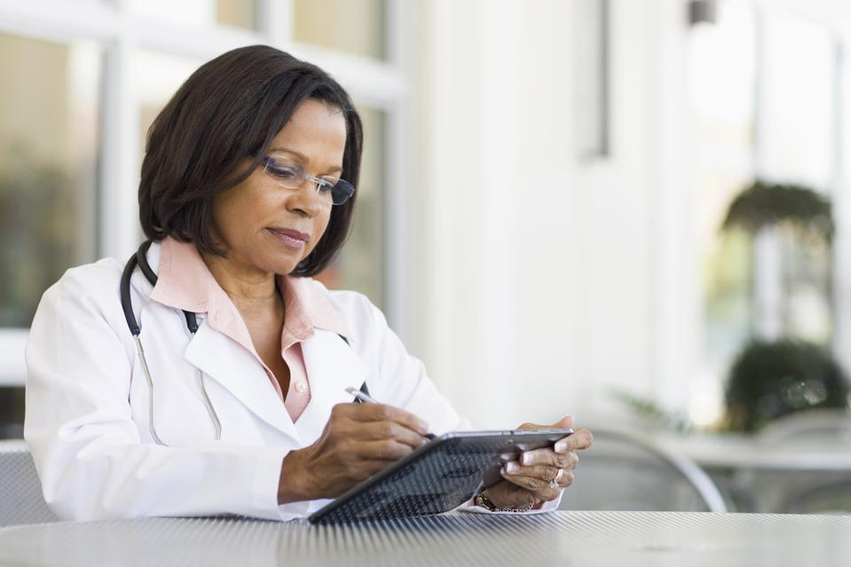 Senior African American female doctor using tablet PC