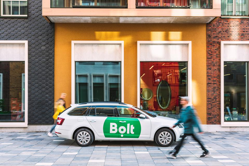 A man walks by a car with Bolt's branding.