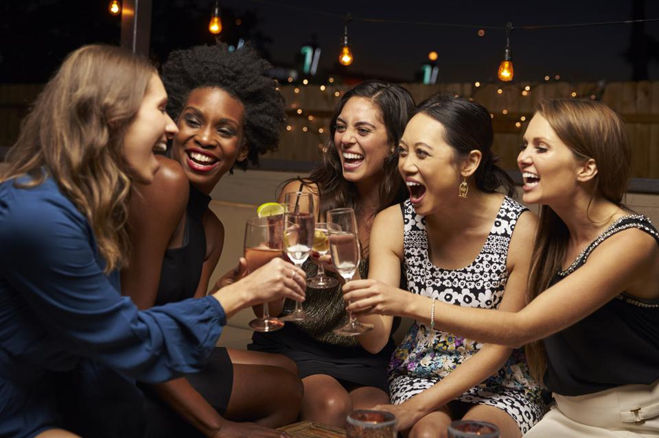 Female friends enjoy night out at rooftop bar