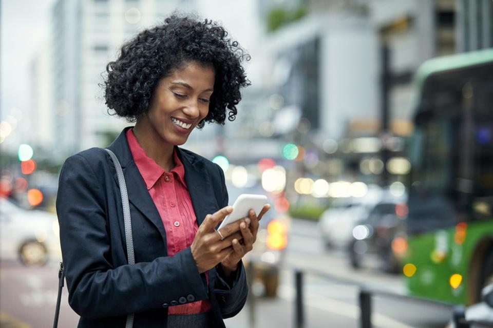 Smiling businesswoman surfing net on mobile phone