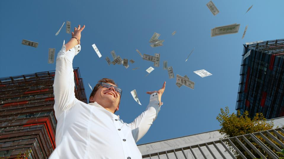 CLOSE UP: Smiling man celebrating winning the lottery by tossing money in air