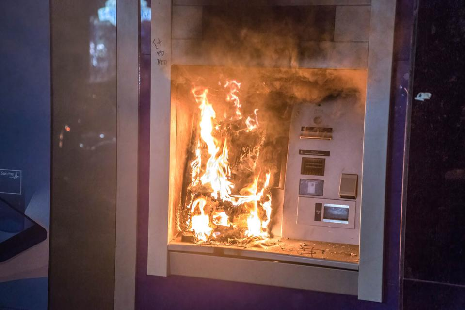 An ATM seen on fire during the demonstration. Protesters...