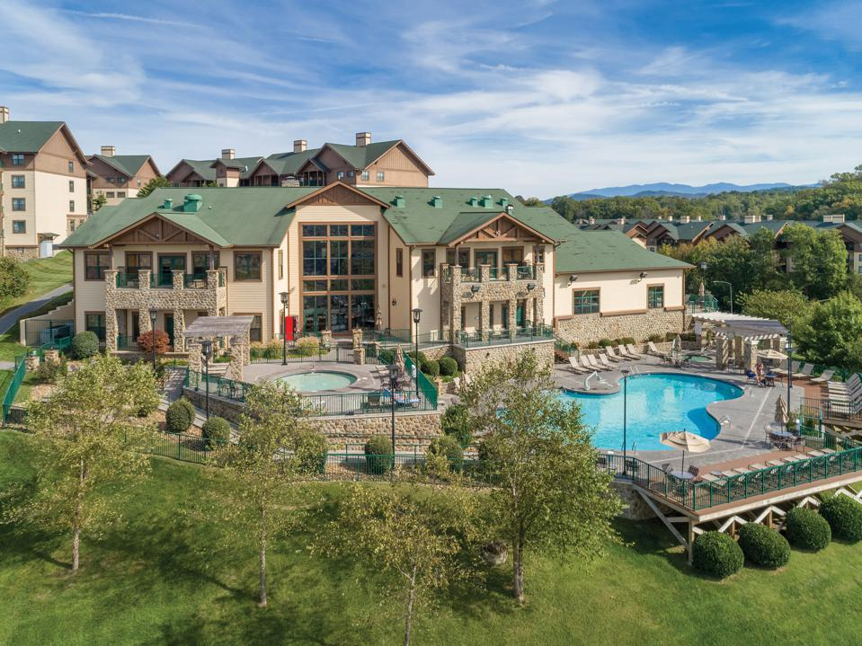 A two-story lodge set behind a swimming pool in the foothills of green mountains.