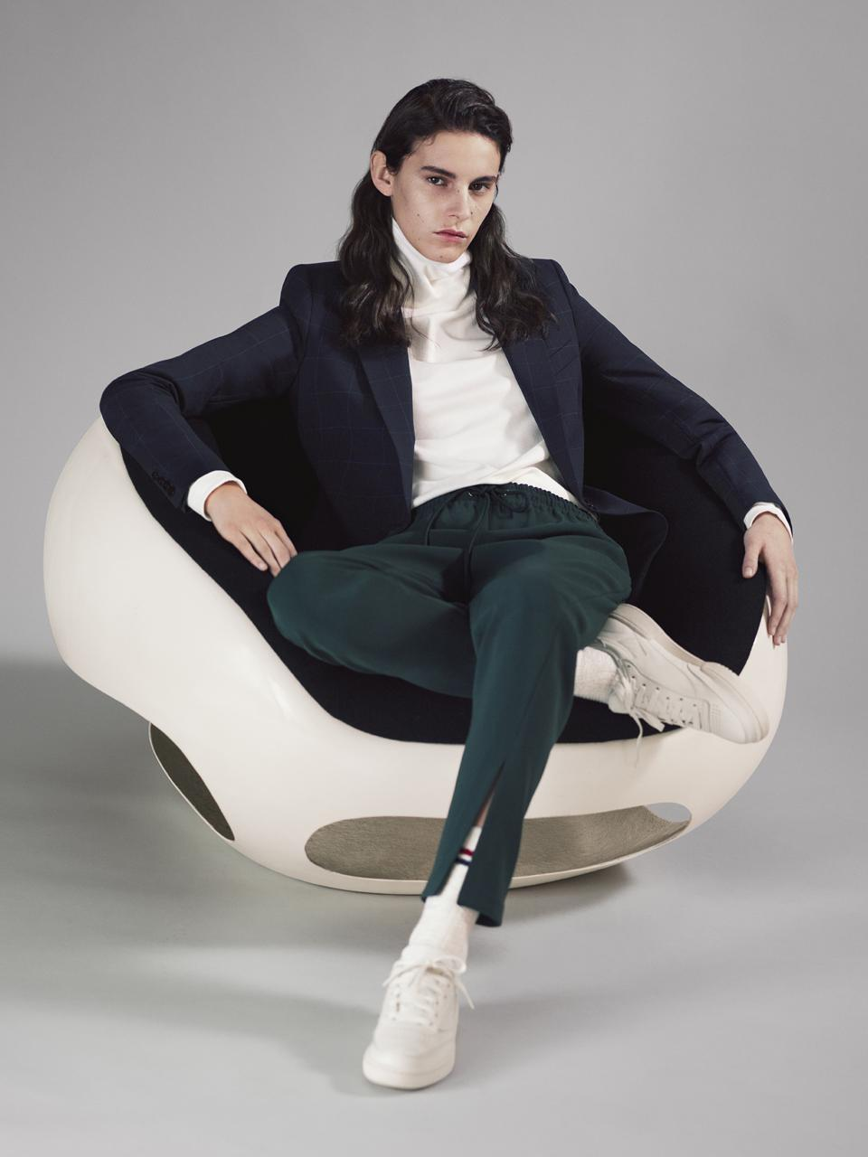 Model sitting a chair in navy blue blazer, turtleneck and green pants.