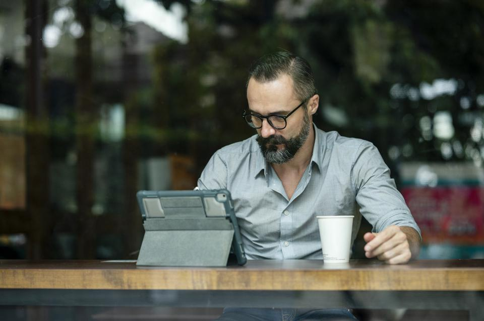 Front View of a Confidence man working online at a cafe using a digital tablet. Portability, Flexibility, City life.