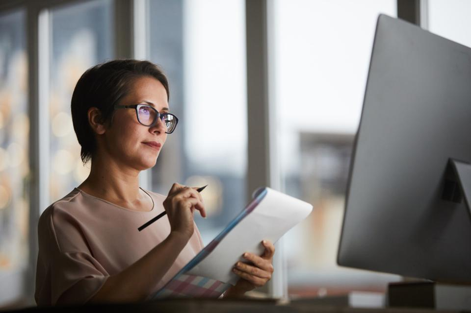 Businesswoman analyzing data with pen, pad, and computer