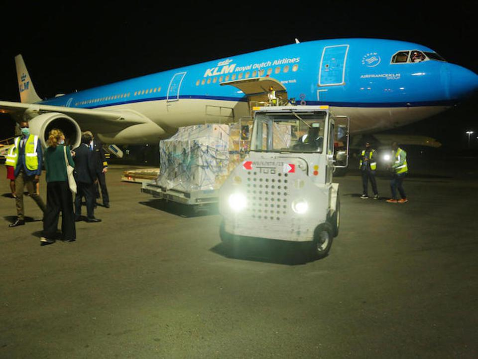 A plane loaded with COVAX COVID-19 vaccine doses lands at night in Rwanda.
