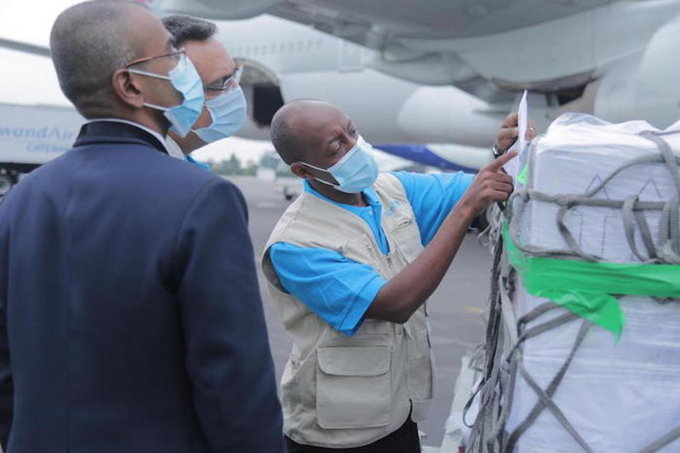 On March 3, 2021, UNICEF Supply Officer Mr. Denis Mupenzi, center, inspects the cargo containing 240,000 doses of the AstraZeneca COVID-19 vaccine at Kigali International Airport in Rwanda.