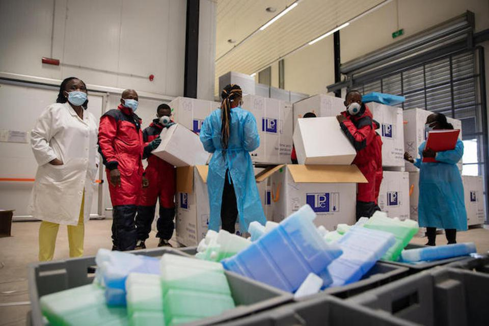 In Kinshasa, Democratic Republic of the Congo, staff at the vaccine storage warehouse in Kinkole commune unpack COVID-19 vaccines in the cold room.