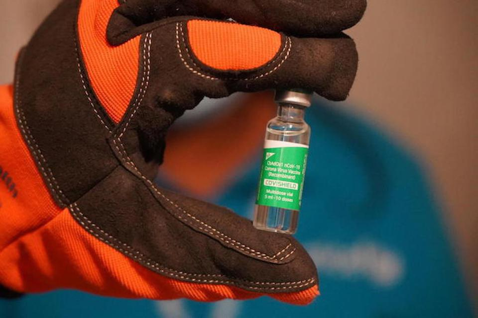 The gloved hand of a worker in a vaccine storage cold room holds a vial containing COVID-19 vaccine.