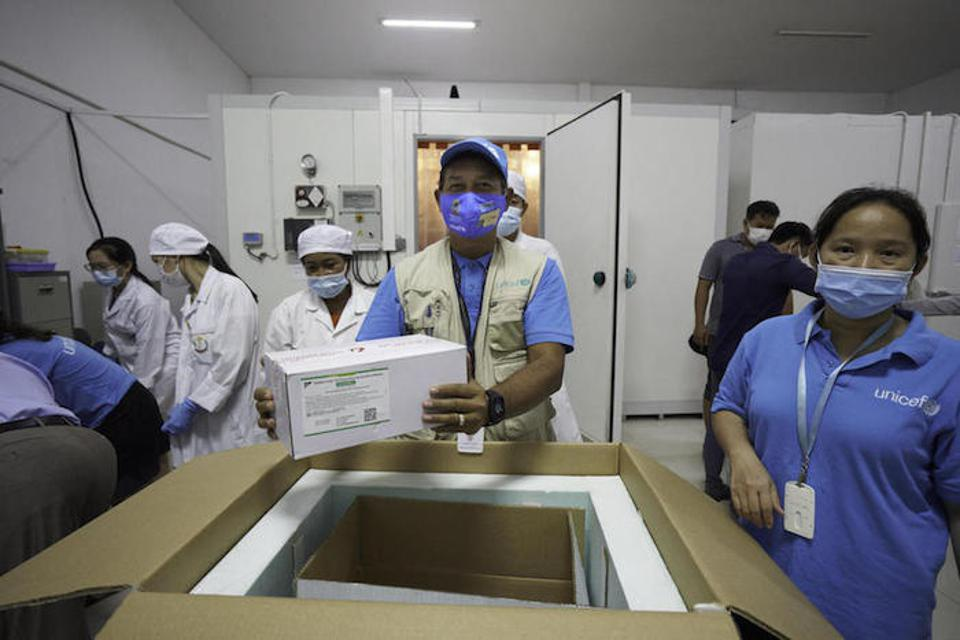 Workers in Cambodia unload COVID-19 vaccine dosees on March 2.