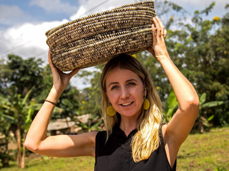 Wallace stands in a field with a woven basket on her head