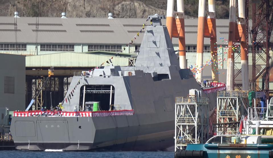 Balloons fly as frigate Mogami slips into water at launch ceremony at Japanese shipyard.