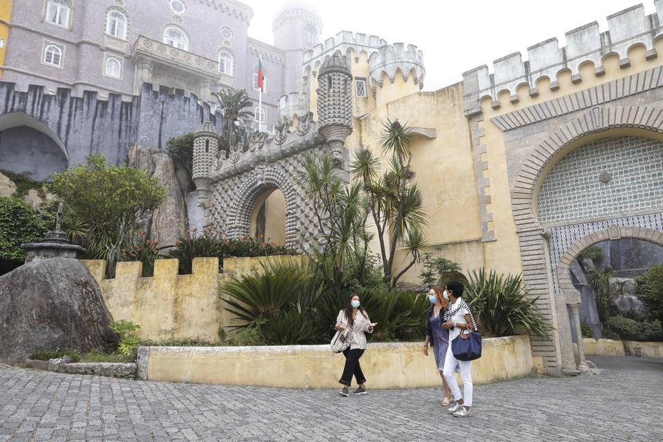 A guide leads two visitors around Pena Palace in Sintra, Portugal