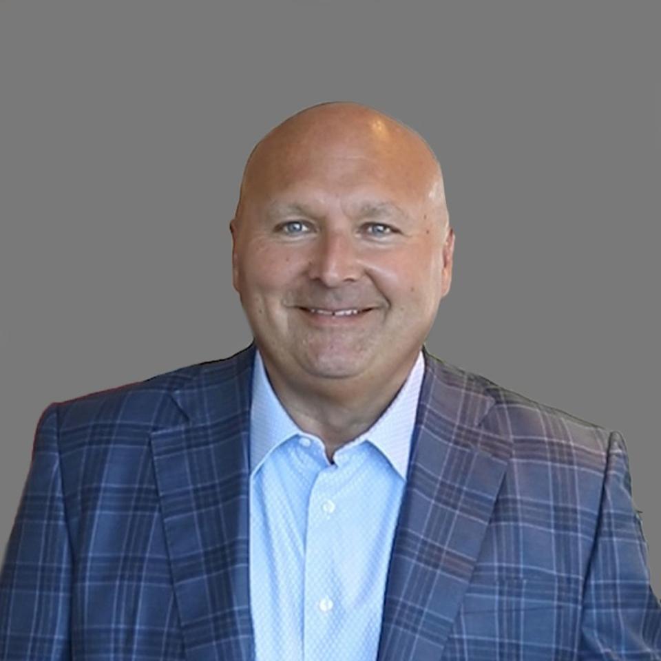 Dennis Berger, bald man with grey eyes, smiling at camera.