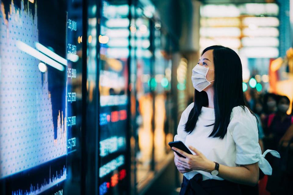 Economic and financial impact during the Covid-19 health crisis deepens. Businesswoman with protective face mask checking financial trading data on smartphone by the stock exchange market display screen board in downtown financial district showing stock m