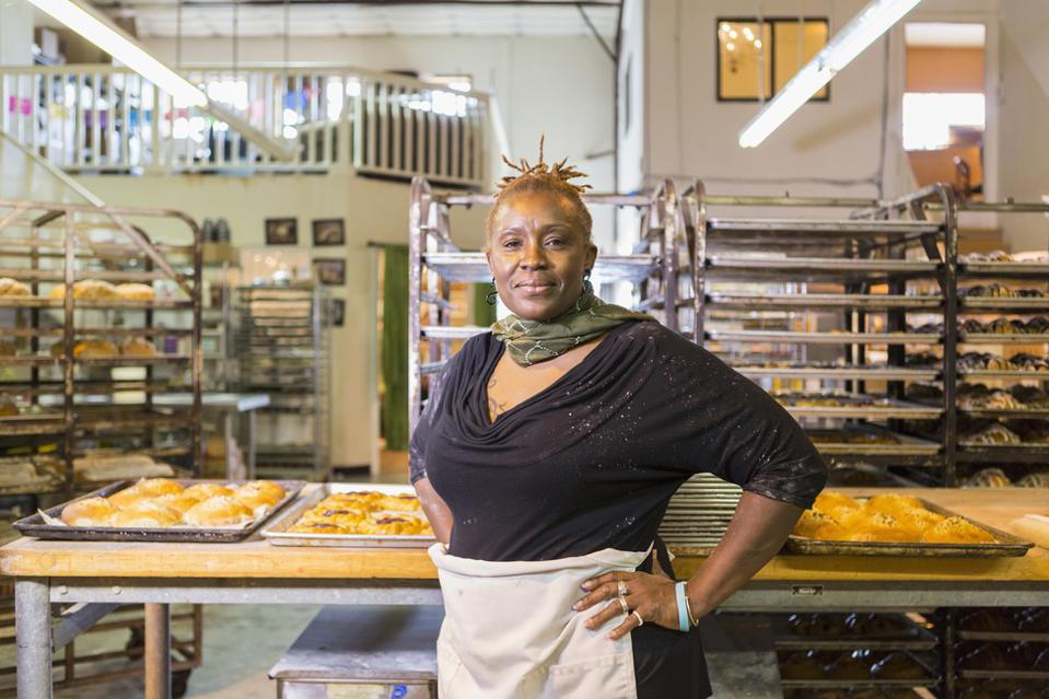 Woman confident in her new management job at a bakery