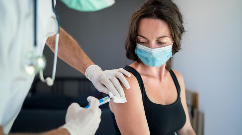 Woman with face mask getting vaccinated.