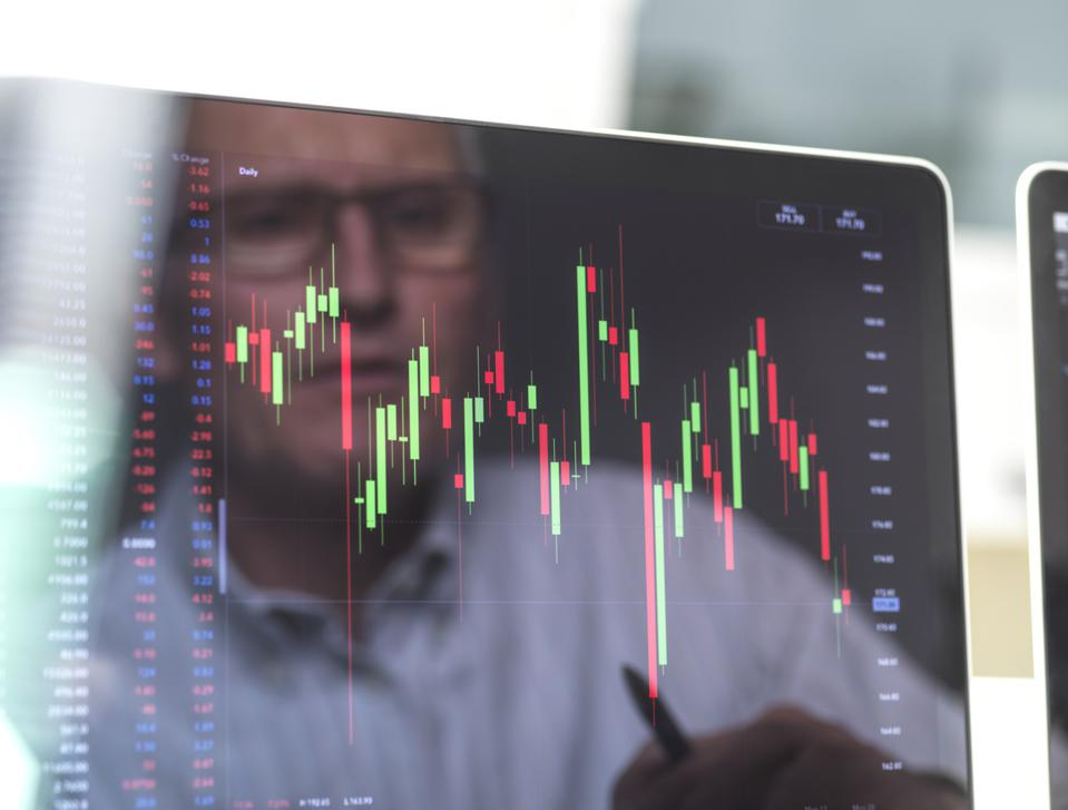Reflection of a stock trader viewing data on a computer screen