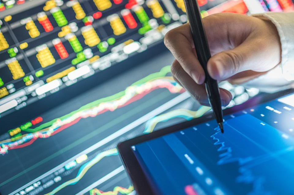 Person with pen analyzing stock market chart on tablet