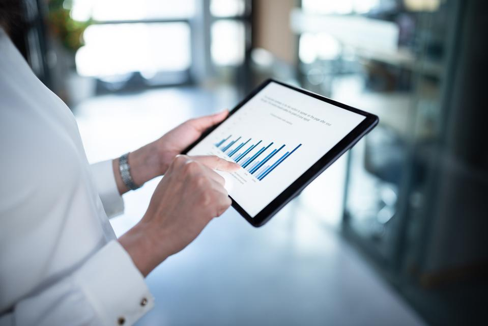 Businesswoman checking financial data on digital tablet