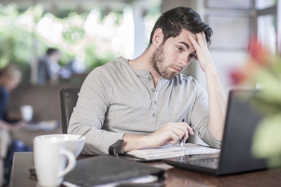 Frustrated young man sitting at dining room table working at home, remote work, video meetings