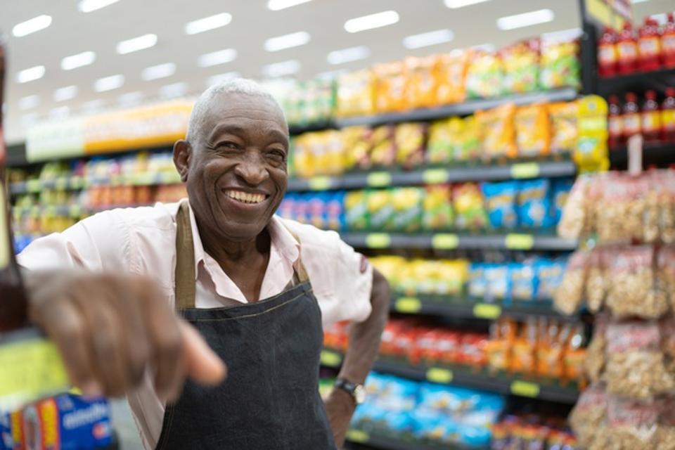 Afro senior man business owner / employee at supermarket